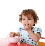 Child eating. Baby girl eat sitting at table on isolated Royalty Free Stock Images