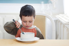 Child eating. Small child boy eating a soup in a restaurant stock photography
