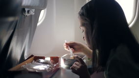 Child is eating in the airplane stock video footage