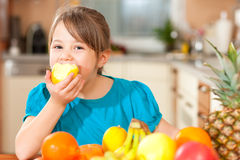 Child eating an apple. Healthy eating - child eating an apple, lots of fresh fruit on the table in front Royalty Free Stock Photography