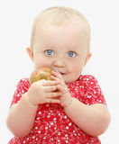 Child eating apple. Child baby girl eating / holding a healthy apple stock images