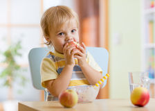 Child eating apple at dinner in nursery at home Royalty Free Stock Images
