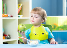 Child eating apple at dinner in nursery at home Royalty Free Stock Photos
