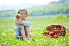 Child eating apple in a field Stock Photography