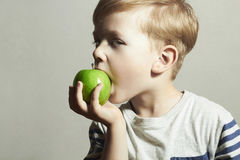 Child eating apple.Little Boy with green apple. Health food. Fruits Royalty Free Stock Photography