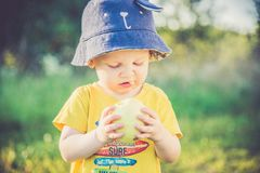 Child eating apple outdoors. Yellow t-shirt, apple in hand stock photography