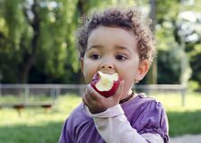 Child eating apple. Child child eating an apple in a park in nature Royalty Free Stock Image