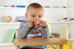 Child eating baby food porridge with spoon Royalty Free Stock Images