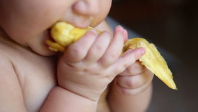Child eating a banana with the skin. Close stock footage