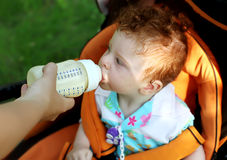 Child eating from bottle Stock Images