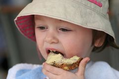 Child eating a bread. A 3 years old girl eating breakfast bread Stock Photography