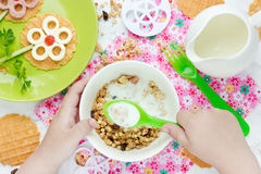 Child eating breakfast cereals with nuts, raisins, candied fruit Royalty Free Stock Photography