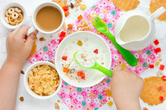Child eating breakfast cereals with nuts, raisins, candied fruit Royalty Free Stock Photos
