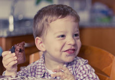 Child eating brownie. Little boy eating a piece of brownie with a cute smile Royalty Free Stock Images