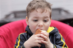 Child eating bun Stock Images