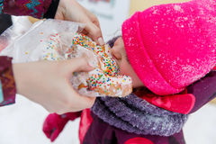 Child eating bun in winter Stock Photography