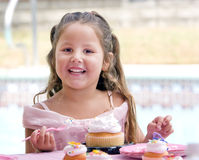 Child Eating Cake. A Hispanic girl (5 years old) wearing pink party dress eating birthday cupcake Royalty Free Stock Photography