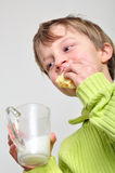 Child eating cake and drinking milk. Portrait of an elementary age boy eating cake and drinking milk royalty free stock images