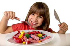 Child eating candy like crazy in sugar abuse and unhealthy sweet nutrition concept Royalty Free Stock Photos