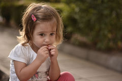 Child eating candy on the street. Cute child eating candy on the street. Blond girl.  Shine. Street Stock Images