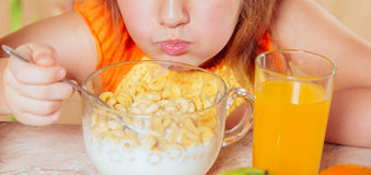 Child is eating cereal flakes Stock Images