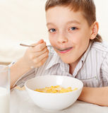 Child eating cereals with milk Royalty Free Stock Photography