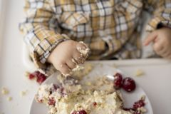 Child eating a cheese cake with his hands. It`s very healty to let a child eating a cheese cake with his hands royalty free stock photo