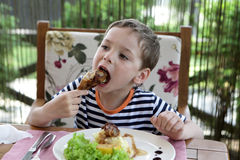 Free Child Eating Chicken Leg Royalty Free Stock Photography - 74505707