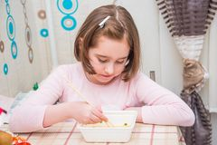 Child is eating Chinese noodles with chopsticks. Child is eating Chinese noodles for the table, disposable tableware, chopsticks Royalty Free Stock Image