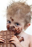 Child eating chocolate. Baby with face covered in chocolate Stock Photos