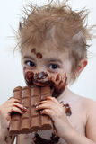 Child eating chocolate. Baby with face covered in chocolate Stock Images
