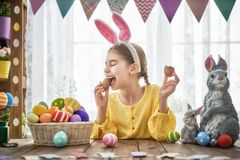 Child is eating chocolate eggs. Beautiful child is eating chocolate eggs. Happy family preparing for Easter. Cute little girl is wearing bunny ears royalty free stock image