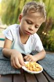 Child eating crackers. At table in cafe stock photo