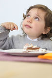 Child eating cream cake Royalty Free Stock Images