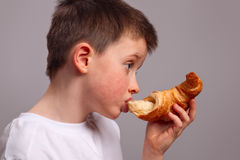 Child eating a croissant stock image