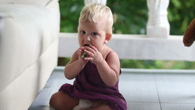 Child eating cucumber standing leaning on the sofa stock video footage