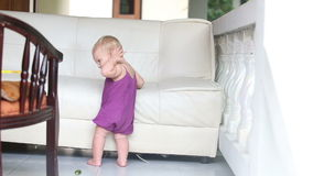 Child eating cucumber standing leaning on the sofa stock footage