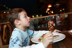 Child eating cutlet. At table in restaurant royalty free stock photos