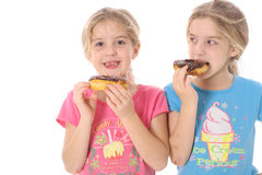 Child eating a doughnut looking at her sister Stock Photo