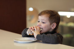 Child eating eclair Royalty Free Stock Photo