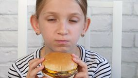 Child eating fast food, kid eats hamburger in restaurant, girl drinking juice.  stock video footage
