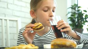 Child eating fast food, kid eats hamburger in restaurant, girl drinking juice.  stock footage