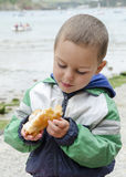 Child eating fish outdoors Stock Photo