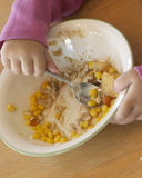 Child eating food in bowl. Close up of child finishing meal royalty free stock photos