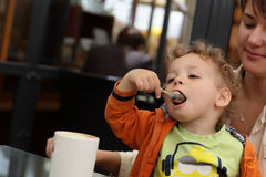 Child eating froth of coffee Royalty Free Stock Images