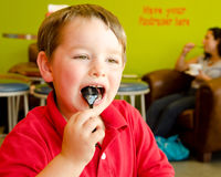 Child eating frozen yogurt at shop. Young boy eating chocolate frozen yogurt at frozen yogurt or ice cream shop Stock Photos