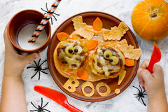Child eating funny Halloween dinner mummy meatbolls with sauce a. Nd crispy bat tortilla top view Stock Photo
