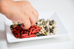 Child eating goji and other seeds Stock Photo