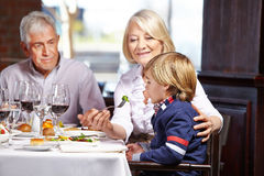 Child eating with grandparents Royalty Free Stock Photo