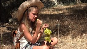 Child eating grapes, hungry tourist little girl eats fruits in olive orchard 4K stock footage